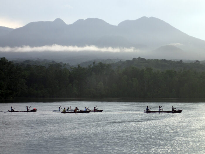 Community members in the Solomon Islands paddle in traditional boats off the coast. Credit: © Stacy Jupiter